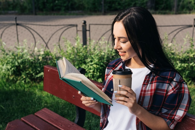 Het glimlachen van het jonge boek van de vrouwenlezing met het houden van beschikbare koffiekop terwijl het zitten op bank bij park Gratis Foto
