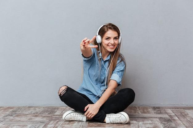 Het glimlachen van het luisteren van de vrouw muziek op de vloer Gratis Foto