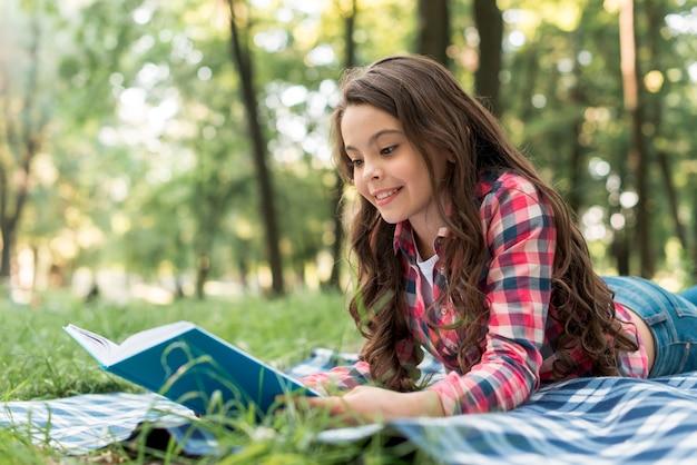 Het glimlachen van het mooie boek van de meisjeslezing terwijl het liggen op geruite deken bij park Gratis Foto