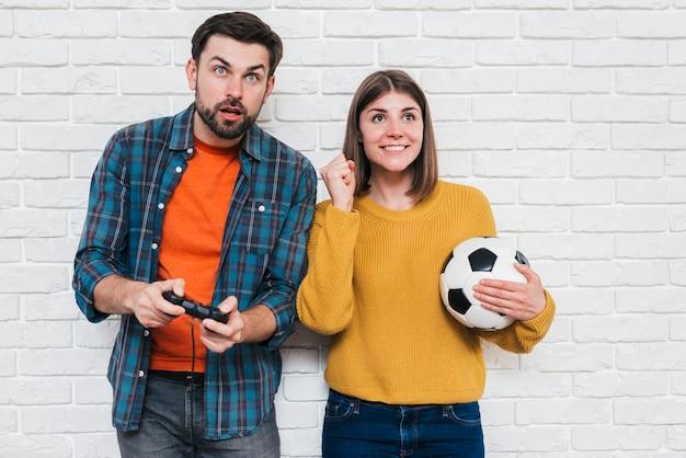 Het glimlachen van jonge in hand het voetbalbal van de vrouwenholding die haar vriend het spelen videospelletje toejuichen Gratis Foto