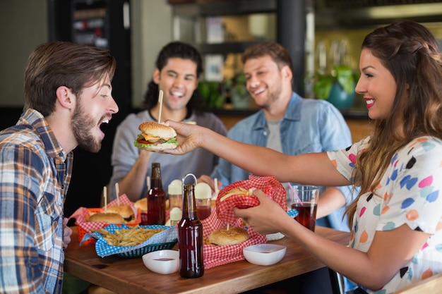 Het glimlachen van vrouwen voedende hamburger aan mannelijke vriend Premium Foto