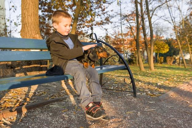 Het glimlachen van weinig jongen en hondzitting op bank in de herfstpark Premium Foto