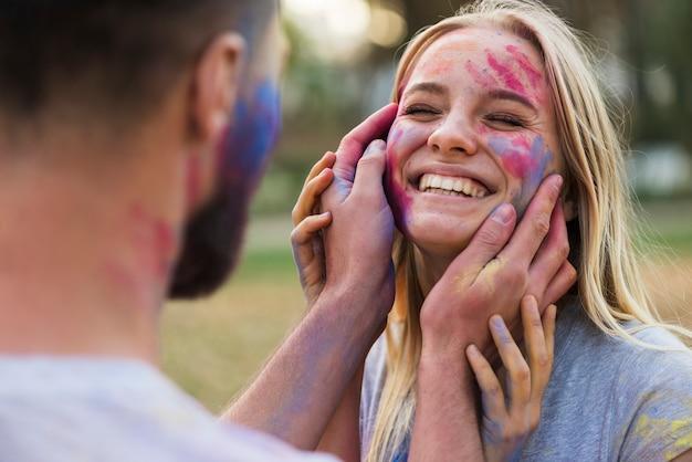 Het glimlachen vrouw het stellen met gekleurd gezicht Gratis Foto