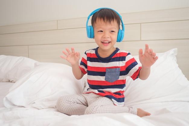 Het glimlachende aziatische kind dat van de peuterjongen gestreepte t-shirt draagt die aan muziek in hoofdtelefoons & het dansen luistert Premium Foto