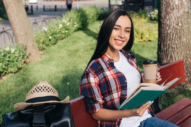 Het glimlachende boek van de vrouwenholding en beschikbare koffiekop terwijl het zitten op bank bij park Gratis Foto