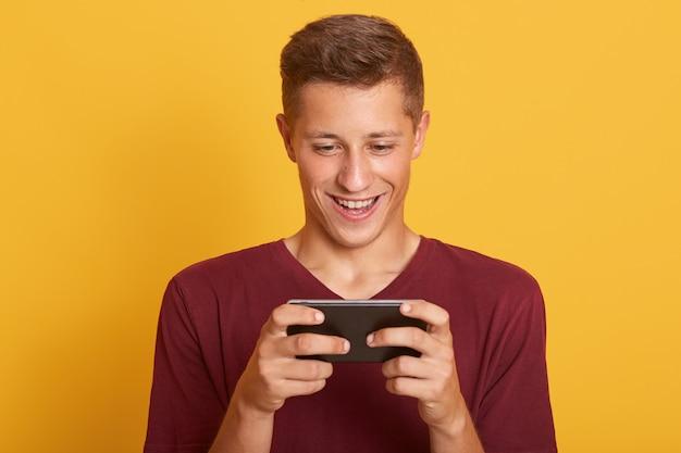 Het glimlachende jonge mensen speelspel op smartphone, kijkt gelukkig en geconcentreerd, glimlachend kijkend op het scherm van zijn apparaat Gratis Foto