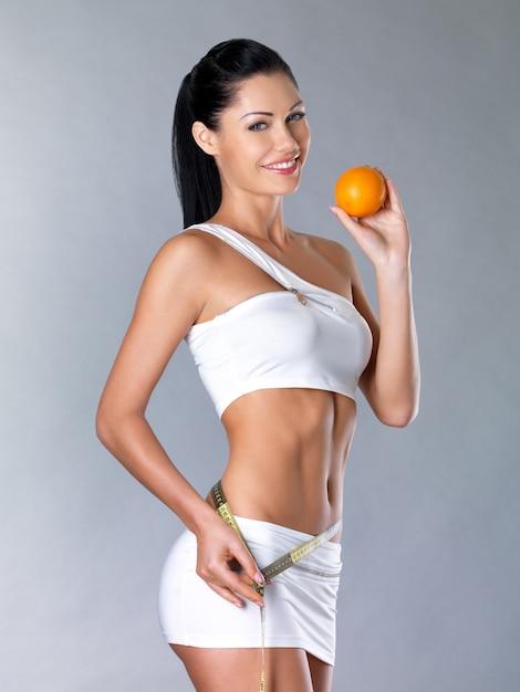 Het glimlachende meisje meet cijfer met een meetlint en houdt de sinaasappel vast. gezonde levensstijl cocnept. Gratis Foto