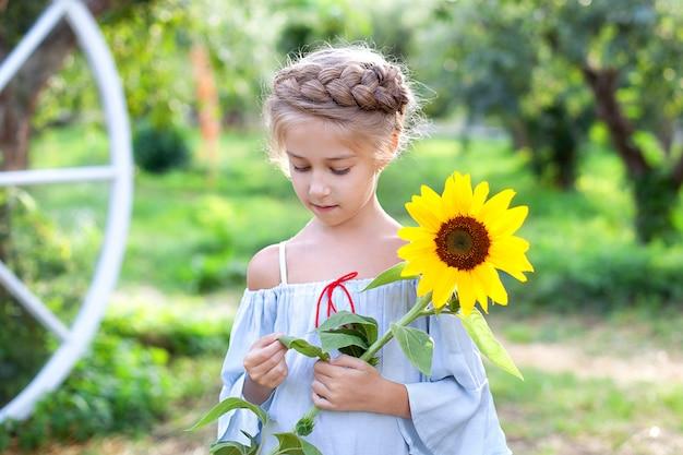 Het glimlachende meisje met een vlecht op haar hoofd houdt zonnebloem in tuin. closeup portret jonge blonde meisje met zonnebloem. Premium Foto