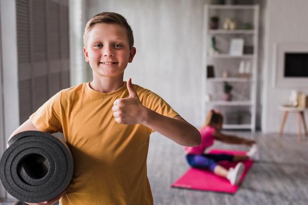 Het glimlachende portret van een jongensholding rolde op oefeningsmat die duimen teken omhoog tonen Gratis Foto