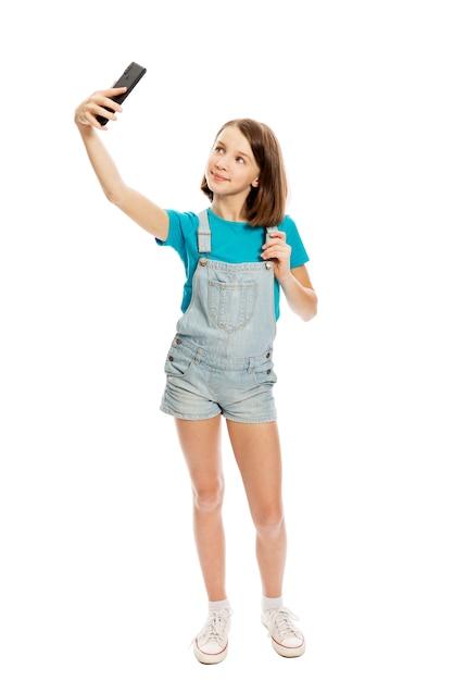 Het glimlachende tienermeisje wordt gefotografeerd op de telefoon. volledige hoogte. geã¯soleerd op een witte achtergrond. Premium Foto