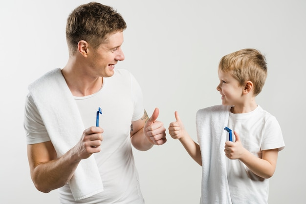 Het glimlachende vader en zoons in de hand houden van scheermes die duim tonen ondertekent omhoog op witte achtergrond tegen witte achtergrond Gratis Foto