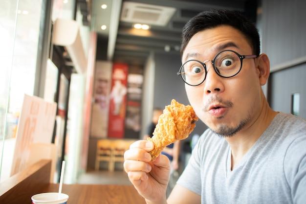 Het grappige gezicht van de mens eet gebraden kip in het concessiekoffie. Premium Foto