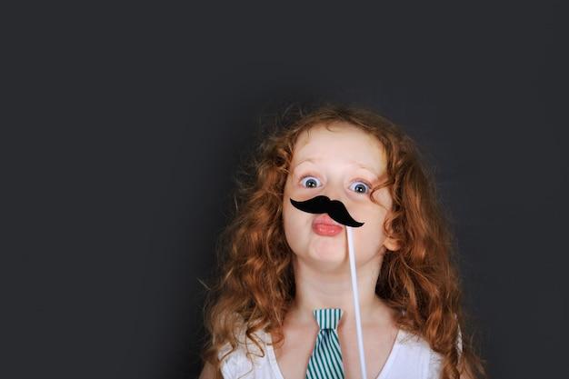 Het grappige meisje houdt carnaval-snor en verzendt luchtkussen. Premium Foto