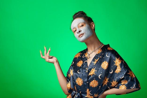Het grappige meisje van yong met het masker van de kleischoonheid op huid geïsoleerd model Premium Foto