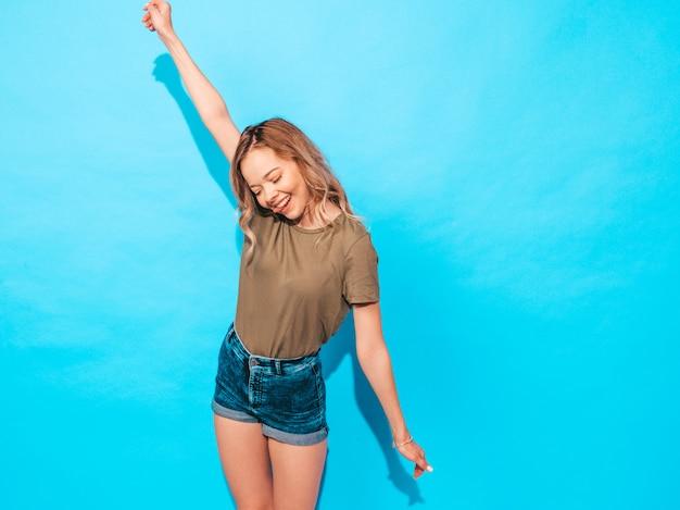 Het grappige model stellen dichtbij blauwe muur in studio. heft haar handen op Gratis Foto
