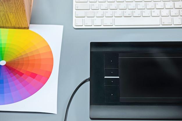 Het grijze bureau met laptop, notitieblok met blanco vel, pot met bloem, stylus en tablet voor retouchering Gratis Foto