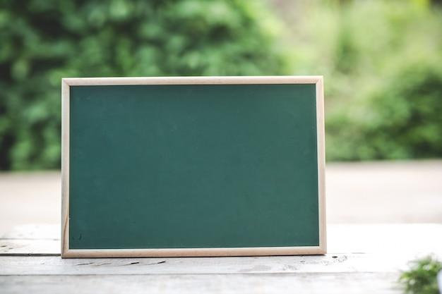 Het groene bord is leeg voor het plaatsen van tekst op de houten vloer. Gratis Foto