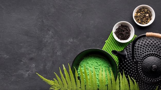 Het groene poeder van de matchethee met droog kruid op zwarte achtergrond Gratis Foto
