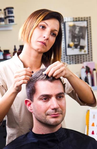 Het haar van de gelukkige vrouwelijke herenkapper het plaatsen cliënt Premium Foto