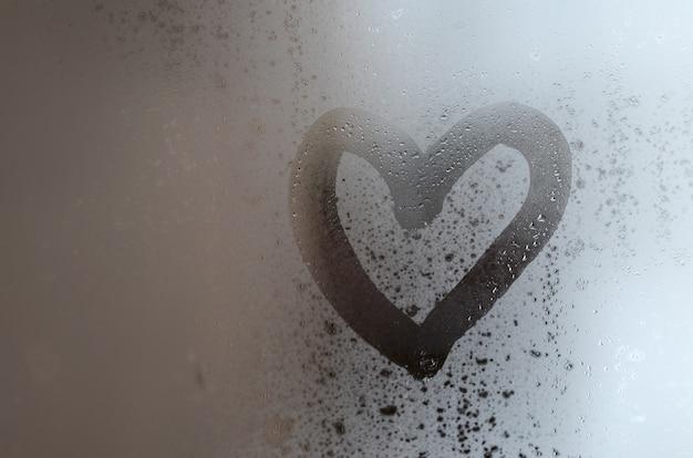 Het hart is in de winter op het beslagen glas geschilderd Premium Foto