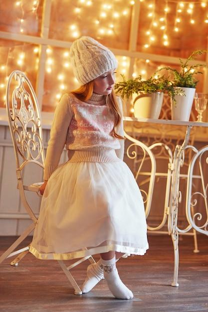 Het heldere roodharige meisje in een witte hoed en een mooie jurk zit in een herfstcafé. roodharige meisje met grote blauwe ogen en een mooie trui voldoet aan de lente Premium Foto