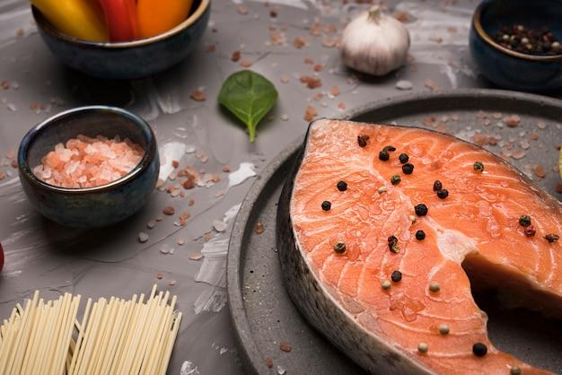 Het hoge lapje vlees van de hoek ruwe zalm op dienblad met ingrediënten Gratis Foto