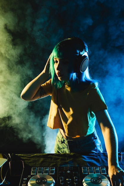 Het hoge leven van de nachtnachtclub met kleurrijke rook en vrouwelijk dj Gratis Foto