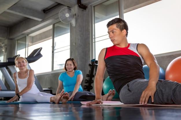 Het hogere groep aantrekkelijke uitrekken zich bij geschiktheidsgymnastiek. Premium Foto