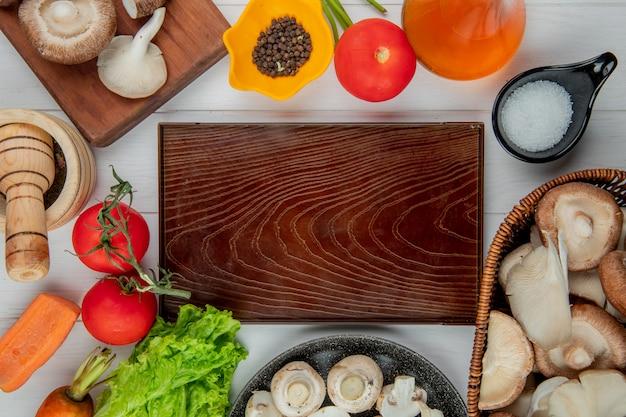 Het hoogste mening van verse paddestoelen in een rieten mand en tomatenfles olijfoliezout en peperbollen schikte rond houten raad op wit Gratis Foto