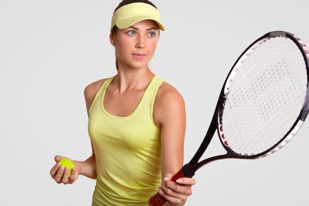 Het horizontale portret van vrij professionele vrouwelijke tennisspeler houdt racket, klaar om favoriet schot te maken, houdt bal Gratis Foto