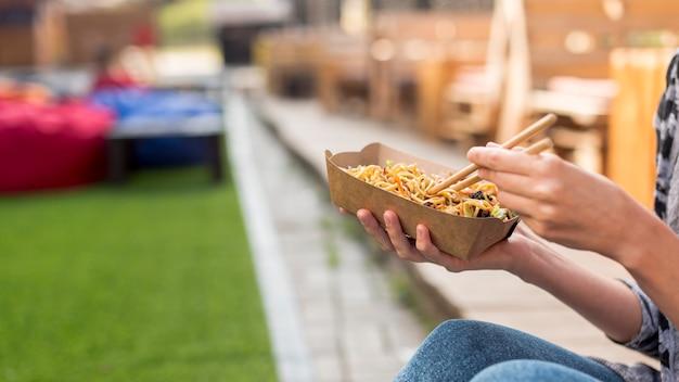 Het houden van chinees voedsel met vage achtergrond Gratis Foto