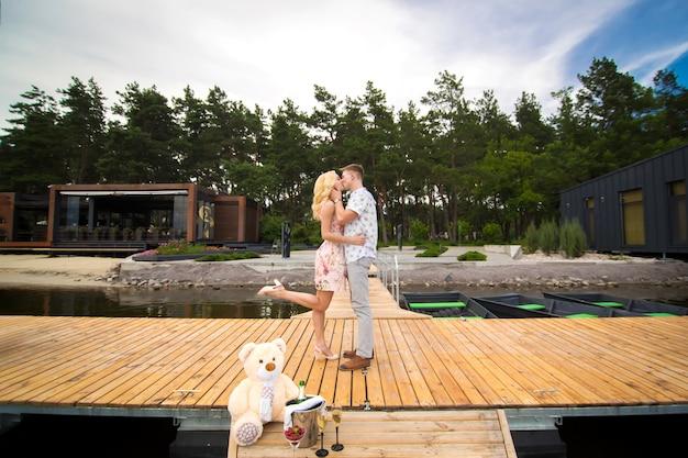 Het houden van van jonge paarkussen op een houten pijler. lovestory op de pier Premium Foto