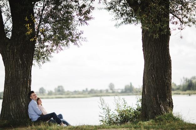 Het houdende van jonge paar koestert en glimlacht in openlucht dichtbij het meer op zonnige dag. liefde en tederheid, dating, romantiek, familieconcept. Premium Foto