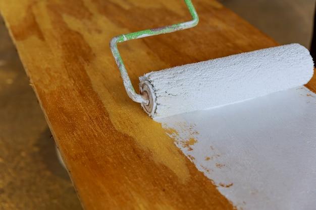 Het hout verven met witte verfroller Premium Foto