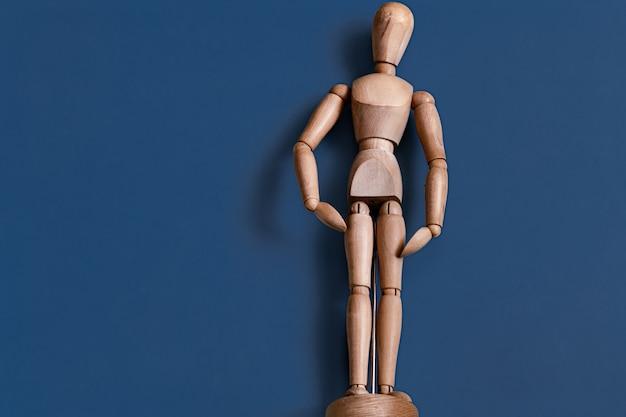 Het houten manbeeldje op blauw. Gratis Foto