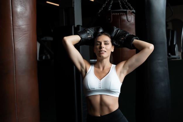 Het in dozen doen vrouw het stellen met bokszak, op dark. sterk en onafhankelijk vrouwenconcept Gratis Foto