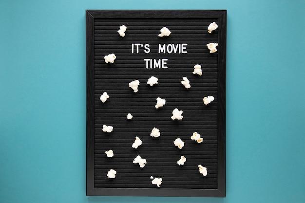 Het is filmtijd belettering op zwarte bord met popcorn Gratis Foto