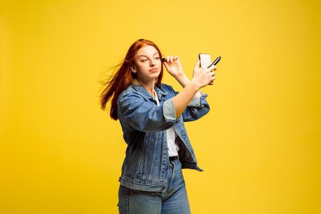 Het is gemakkelijker om een volgeling te zijn. geen selfie nodig voor make-up. kaukasische vrouw portret op gele achtergrond. mooi vrouwelijk rood haarmodel. concept van menselijke emoties, gezichtsuitdrukking, verkoop, advertentie. Gratis Foto