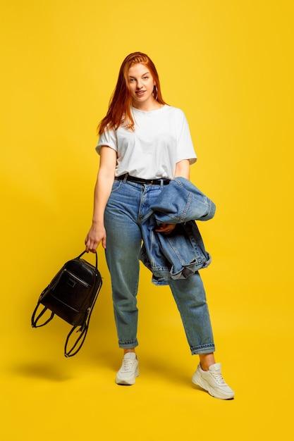 Het is gemakkelijker om een volgeling te zijn. minimale kleding nodig om te gaan. kaukasische vrouw portret op gele achtergrond. mooi vrouwelijk rood haarmodel. concept van menselijke emoties, gezichtsuitdrukking, verkoop, advertentie. Gratis Foto
