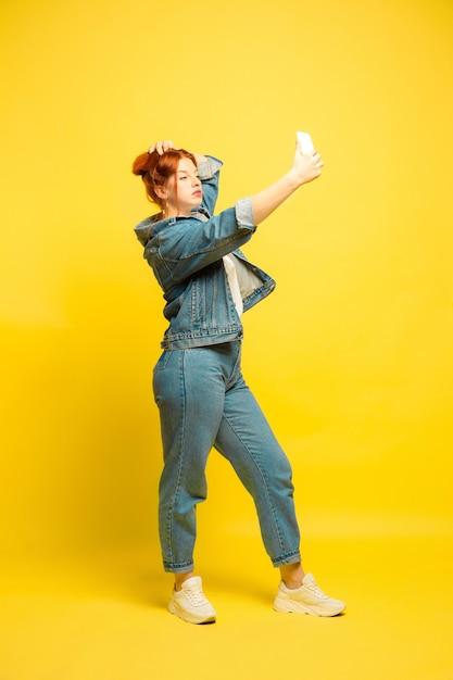 Het is gemakkelijker om een volgeling te zijn. minimale kleding nodig voor selfie. kaukasische vrouw portret op gele achtergrond. mooi vrouwelijk rood haarmodel. concept van menselijke emoties, gezichtsuitdrukking, verkoop, advertentie. Gratis Foto