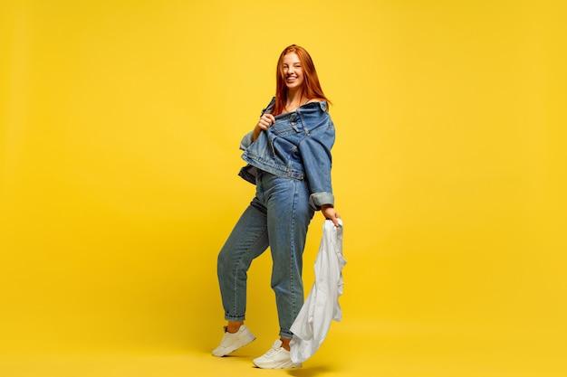 Het is gemakkelijker om een volgeling te zijn. sneller wassen, als het maar één shirt is. kaukasische vrouw portret op gele achtergrond. mooi rood haarmodel. concept van menselijke emoties, gezichtsuitdrukking, verkoop, advertentie. Gratis Foto