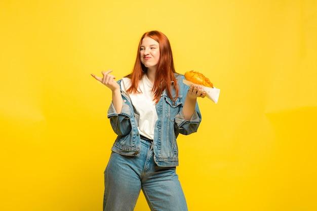 Het is gemakkelijker om een volgeling te zijn. u hoeft geen foto te maken met eten. blanke vrouw op gele achtergrond. mooi vrouwelijk rood haarmodel. concept van menselijke emoties, gezichtsuitdrukking, verkoop, advertentie. Gratis Foto