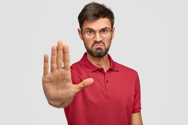 Het is verboden! boze ontevreden jonge man fronst zijn wenkbrauwen, toont stopgebaar, houdt de handpalm vooraan, probeert zichzelf te voorkomen van iets slechts en onaangenaams, draagt een casual t-shirt, geïsoleerd op wit Gratis Foto