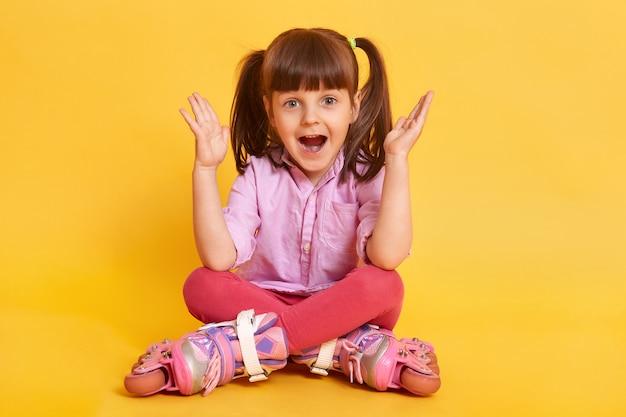 Het jong geitjemeisje in rolschaatsen zit op de vloer bij vrije tekst Gratis Foto