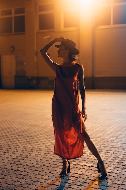 Het jonge, aantrekkelijke meisje in een hoed vormt 's nachts naar de camera Gratis Foto