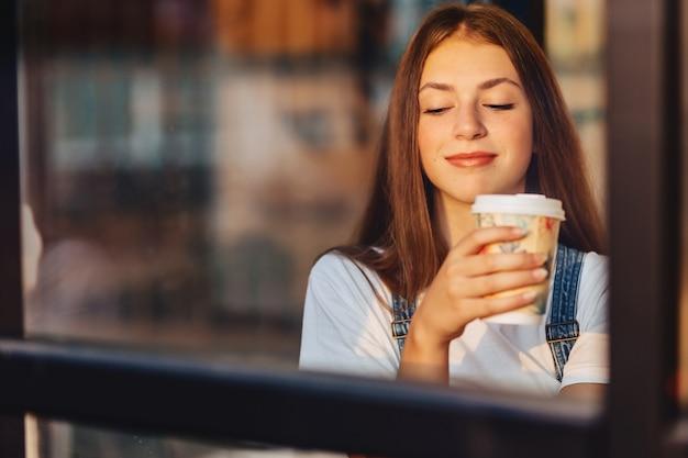 Het jonge aantrekkelijke mooie meisje bij koffie met koffie ontspant bij ochtend throuth glas Premium Foto