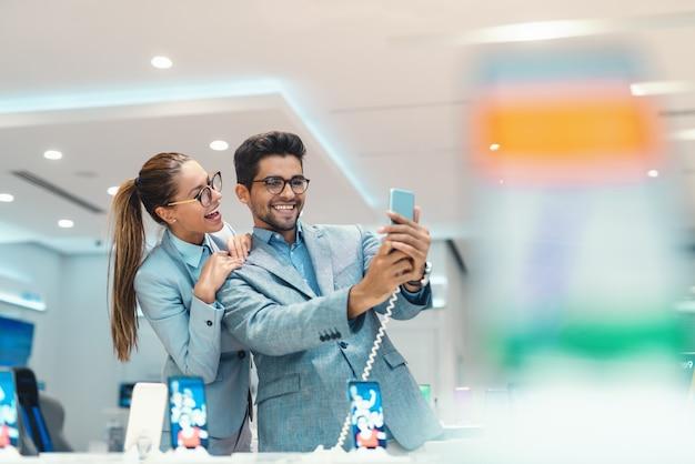 Het jonge aantrekkelijke multiculturele paar kleedde het elegante nemen selfie met nieuwe slimme telefoon in technologie-opslag. Premium Foto