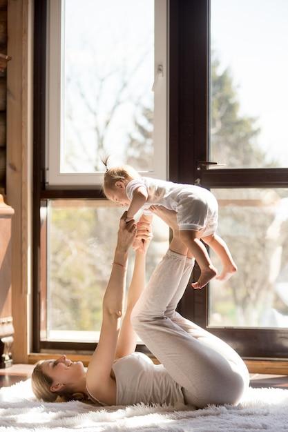 Het jonge aantrekkelijke sportieve moeder en babydochter uitoefenen Gratis Foto