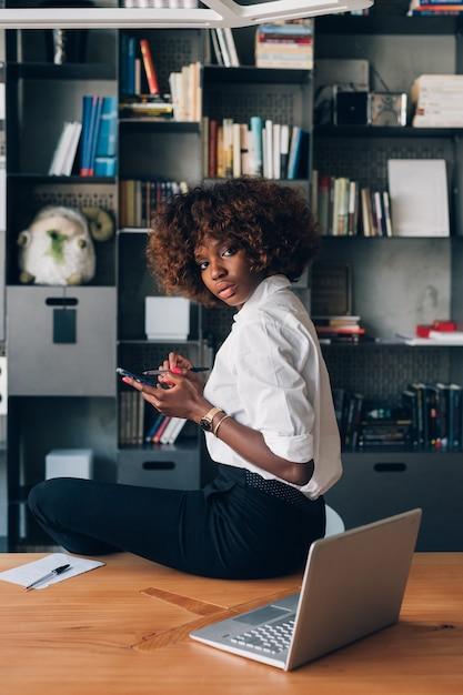 Het jonge afrikaanse vrouw stellen in modern bureau met smartphone en het kijken camera Premium Foto
