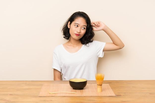 Het jonge aziatische meisje met theematcha die twijfels hebben en verwart gezichtsuitdrukking Premium Foto